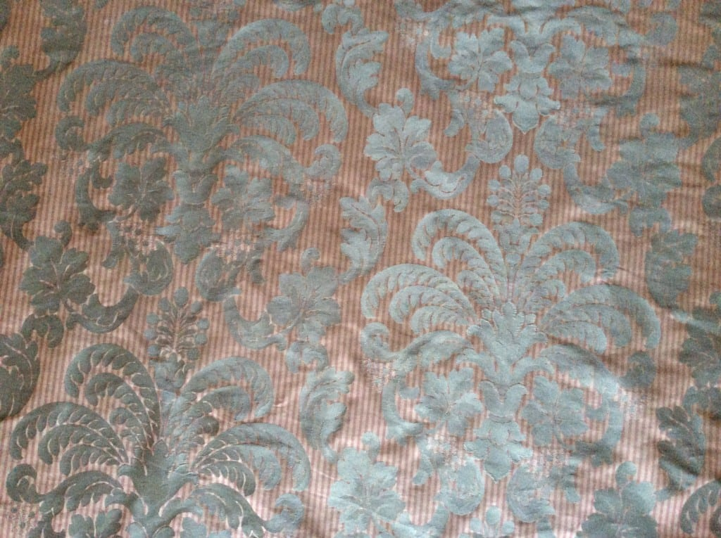 Green damask on a burgundy stripe background. It will look great on my kitchen chairs!