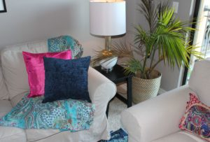 She wanted blue tones in the main living space along with a little bit of fuchsia, so added those colors with the accent pillows, picture frames, and throw, and area rug.