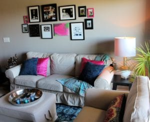 She wanted a collage of décor on her main living room wall. We used some photos she cherished, along with a modern canvas, a variety of frames, and a few additional hangings. It was about adding a unique Boho style that was personalized by her life.
